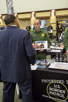 01-27-2017 - Michigan, USA. US Border Patrol Agent recruiting a job seeker at a job fair for veterans and persons with disabilities sponsored by the American Society of Employers © Jim West