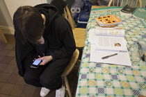14-03-2017 - Teenager taking a break from homework with an Iphone. Revising for A levels. © John Harris