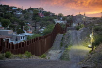 16-04-2017 - Nogales, Arizona, US Mexican border fence separating Nogales, Arizona (R) and Nogales, Sonora. Border Patrol lights illuminate the US side © Jim West