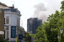 14-06-2017 - Grenfell Tower Fire. View of Grenfell Tower from about half a mile away as smoke can be seen still smouldering a full 12 hours after the raging inferno that engulfed the West London tower block result... © Stefano Cagnoni