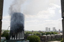 14-06-2017 - Grenfell Tower Fire. Pockets of fire still visible in some flats as smoke is seen still smouldering a full 12 hours after the raging inferno that engulfed the West London tower block seen on the left... © Stefano Cagnoni