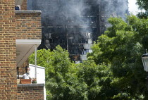 14-06-2017 - Grenfell Tower Fire. Local resident on his balcony wears a mask to filter fumes from the smoke still smouldering a full 12 hours after the raging inferno that engulfed the West London tower block seen... © Stefano Cagnoni