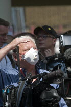 14-06-2017 - Grenfell Tower Fire. TV News camera operator wearing a mask to protect himself from the fumes and smoke a full 12 hours after the raging inferno that engulfed the West London tower block resulting in... © Stefano Cagnoni