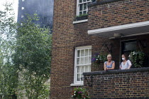 14-06-2017 - Grenfell Tower Fire. Local residents on their balcony one wearing a mask to filter fumes from the smoke still smouldering a full 12 hours after the raging inferno that engulfed the West London tower b... © Stefano Cagnoni