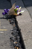 14-06-2017 - Grenfell Tower Fire. Flowers in memory of the victims laid amongst the ash lying in the gutter that fell from the Grenfell Tower fire that engulfed the West London tower block overnight. The note read... © Stefano Cagnoni