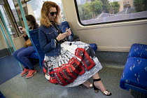30-06-2017 - Passenger with an iconic telephone box skirt on a DLR train, Canary Wharf, London © Jess Hurd