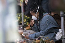 12-07-2017 - Grenfell Tower fire vigil, one month after the fire, London, woman lights a candle at the Memorial Wall with a mask to protect against feared asbestos © Jess Hurd