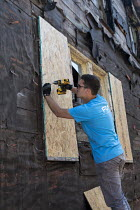 01-08-2017 - Detroit, Michigan, USA Volunteers in a community improvement project called Life Remodeled workers from Fiat Chrysler Automobiles (FCA) boarding up an abandoned house © Jim West