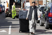 17-09-2017 - Bin workers strike. Resident pursuing refuse collection by contractors with his wheelie bin, Sparkbrook, Birmingham. Strike is costing 40,000 pounds a day. The Labour council have issued redundancies... © John Harris