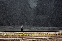 05-09-2017 - Sault Ste. Marie, Ontario Canada - A worker walks past a pile of coal at the Algoma steel mill on the shore of the St. Marys River. © Jim West