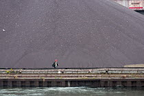 05-09-2017 - Sault Ste. Marie, Ontario Canada - A worker walks past a pile of taconite pellets at the Algoma steel mill on the shore of the St. Marys River. © Jim West