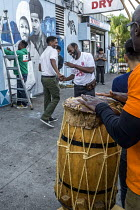 23-10-2017 - Oakland, California, USA, local capoeira group performing on the sidewalk while artists paint a Black Panther Mural on the wall of a liquor store, celebrating the history of the Black Panther Party. T... © David Bacon