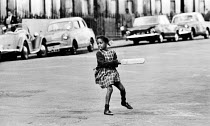24-06-1968 - Young black girl playing cricket in the street, London 1968. Noting Hill West London © Patrick Eagar
