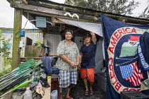 03-11-2017 - Rosharon, Texas USA Cambodian immigrants outside the trailer they lived in with their 7 year old son until it was flooded by Hurricane Harvey. They are part of a community of Cambodian refugees who se... © Jim West