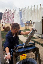 11-08-1962 - Woman drying her washing with a mangle outside her caravan 1962 travellers camp near Slough © Romano Cagnoni