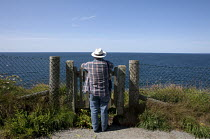 15-07-2015 - Port Issac, Cornwall Tourist admiring the spectacular view of the sea. A gate gives access through a safety fence on the cliff top © David Mansell