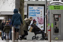 03-02-2018 - Pedestrians walking past a Get Ready For Universal Credit advertisment, Gloucester city centre. Coins dropping into a piggy bank © John Harris