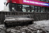 03-03-2018 - Filthy, frozen bench seat due to a burst water main, Globe Town, East London. A bus passing. © Jess Hurd