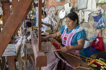 24-02-2018 - San Miguel del Valle, Oaxaca, Mexico - Mexican woman weaving rugs. Microfinance loans from the non profit En Via are supporting small businesses in the village © Jim West