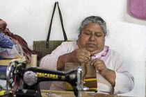 24-02-2018 - Teotitlan del Valle, Oaxaca, Mexico, woman stitching handbags at her home in a small Zapotec village. Microfinance loans from the non profit En Via are supporting small businesses in the village © Jim West