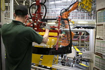 21-08-2017 - Jaguar Land Rover factory, Solihull. Worker preparing a windscreen for a robot arm to fit to a vehicle © John Harris