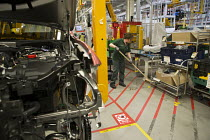 21-08-2017 - Jaguar Land Rover factory, Solihull. Woman assembly worker sweeping the floor whilst the production line has halted © John Harris