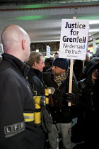 14-12-2017 - Hugging a firefighter, Justice for Grenfell six month anniversary silent walk, Kensington and Chelsea, London © Jess Hurd