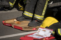 29-06-2018 - Exhausted firefighters from White Watch taking a break with gifted Domino's pizza as Grafton House twelfth floor fire is contained and brought under control by over 50 firefighters at a 22 story East... © Jess Hurd