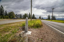 20-07-2018 - Lynden, Washington, USA Border marker between USA and Canada. A road runs on each side of the border, there is no fence or barrier and no visible Border Patrol - unlike the USA Mexican border © David Bacon