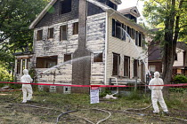 07-30-2018 - Detroit, Michigan, USA workers demolishing an abandoned house wearing protective clothing against asbestos exposure. They are spraying water onto the building to keep asbestos from becoming airborne © Jim West