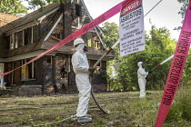 30-07-2018 - Detroit, Michigan, USA workers demolishing an abandoned house wearing protective clothing against asbestos exposure. They are spraying water onto the building to keep asbestos from becoming airborne © Jim West