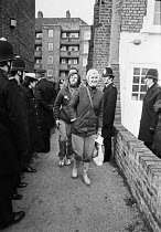 09-01-1981 - Squatters from Kilner House, Kennington, South London are evicted 1981, but come out smiling and defiant. The squat was well-organised and peaceful. The flats at the council housing estate were refurb... © NLA