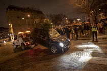08-12-2018 - Paris, France protest by Yellow Vest movement, Champs Elysees area. Damaged Mini car with a christmas tree sticking out from the sunroof is towed away © Jess Hurd