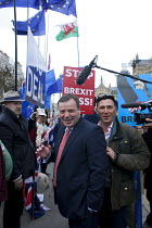 27-03-2019 - Arron Banks (L) co-founder of the  Leave.EU campaign and Andy Wigmore (R) walking through Remain anti Brexit protest opposite the Houses of Parliament, Westminster, London © David Mansell
