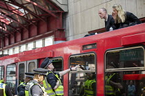 17-04-2019 - Extinction Rebellion stop DLR trains at Canary Wharf, against lack of government action on climate change. Nonviolent direct action blocking London. Police removing protestor glued onto the roof of a... © Jess Hurd