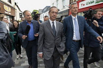 15-05-2019 - Nigel Farage Brexit Party walking down the High Street pursued by a questioning presenter Matt Frei, Merthyr Tydfil, South Wales, Nathan Gill (R) © John Harris