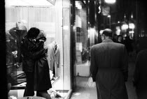 08-09-1961 - Man looking at couple kissing in shop doorway Soho London 1961Man looking at couple kissing in shop doorway Soho London 1961Man looking at couple kissing in shop doorway Soho London 1961Man looking at... © Romano Cagnoni