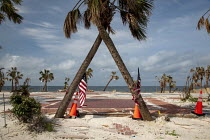 10-05-2019 - Mexico Beach, Florida, USA: Palm trees and flags where a beach house was destroyed. Destruction from Hurricane Michael 7 months after the storm hit the Florida Panhandle © Jim West