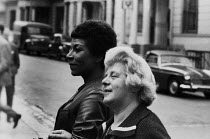 09-03-1963 - Solidarity with American Civil Rights Movement protest, 1963, Notting Hill, London. Black and white women arm in arm together © Romano Cagnoni