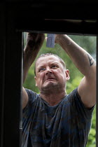 09-07-2019 - Glazier struggling with fitting a double glaized door glass unit © John Harris