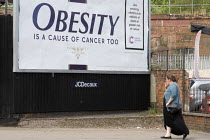 16-07-2019 - Obesity is a cause of cancer too advertisement Cancer Research UK obesity campaign, which highlights excess weight as a cause of cancer. The billboard looks like a cigarette packet. Some members of th... © John Harris