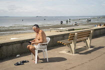 08-08-2019 - Man reading his ipad, Southend beach, Essex. © Jess Hurd