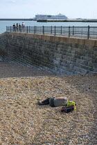 15-08-2019 - Young man sleeping on a pebble beach, luxury cruise liner, Western Harbour, Dover, Kent © Philip Wolmuth