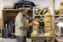10-10-2019 - Michigan, USA: worker stacking wooden bowls, The Holland Bowl Mill, which manufactures bowls and other wood products © Jim West