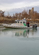 13-12-2019 - Detroit, Michigan USA. US Border Patrol boat cutting through ice on Conners Creek on its way to patrol the Detroit River between the United States and Canada. © Jim West