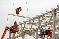 13-12-2019 - Detroit, Michigan USA. Construction workers raising a US flag and a Christmas tree on the last piece of structural steel to be placed on new Fiat Chrysler automobile assembly plant. It is the first ne... © Jim West