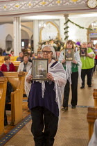 11-01-2020 - Detroit, Michigan USA, Holy Hour, supporting refugees fleeing violence, Most Holy Trinity Catholic Church. Women carrying photographs of children who died in U.S. custody after crossing the border. Th... © Jim West