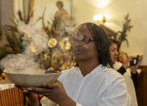 11-01-2020 - Detroit, Michigan USA, Holy Hour, supporting refugees fleeing violence, Most Holy Trinity Catholic Church. Shirlene Smith leeding a processional with a bowl of incense. The event was organized by Stra... © Jim West