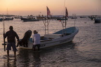 04-02-2020 - Puerto Escondido Beach, Oaxaca, Mexico - Fishermen preparing their fishing boat for a sport fishing trip. © Jim West