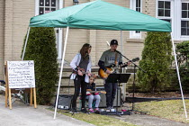 26-03-2020 - Michigan USA Brother and sister playing a porch concert for their neighbours. They have played a concert every evening since Michigan Governor Gretchen Whitmer ordered residents to